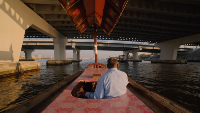 middle eastern man takes solo trip along dubai creek at sunset - cultures stock videos & royalty-free footage