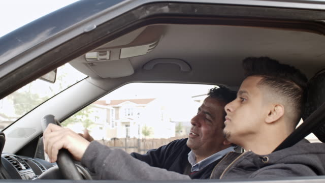 vídeos y material grabado en eventos de stock de middle eastern man teaching son to ride a car - aprender a conducir