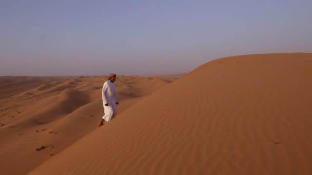 Middle Eastern man walking up desert dunes