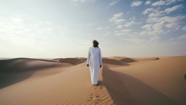 middle eastern man walks along dunes in desert - middle eastern ethnicity stock videos and b-roll footage