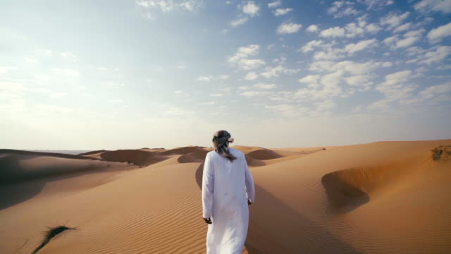 middle eastern man walks along dunes in desert - dish dash stock videos & royalty-free footage