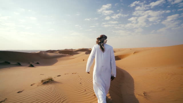 Middle Eastern man walks along dunes in desert