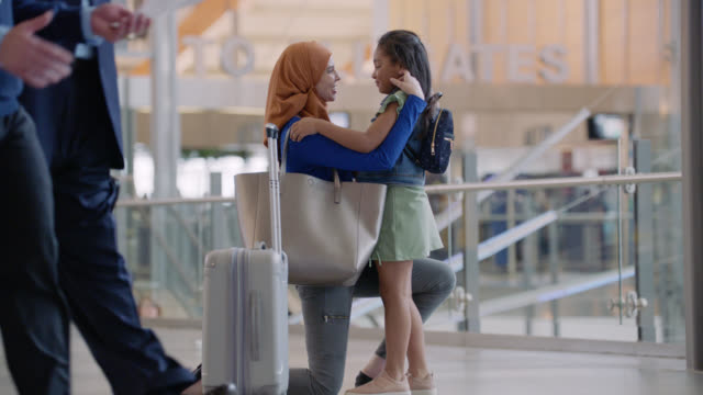 slo mo. middle eastern mother and young daughter greet each other in airport terminal. - nahöstlicher abstammung stock-videos und b-roll-filmmaterial