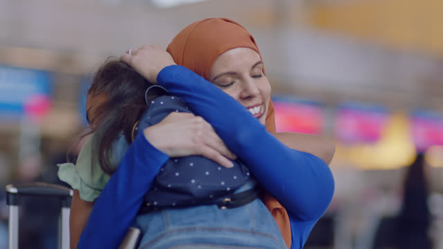 middle eastern mother and young daughter run to each other and embrace in airport terminal. - greeting stock videos & royalty-free footage