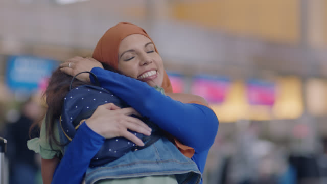 SLO MO. Middle Eastern mother and young daughter run to each other and embrace in airport terminal.
