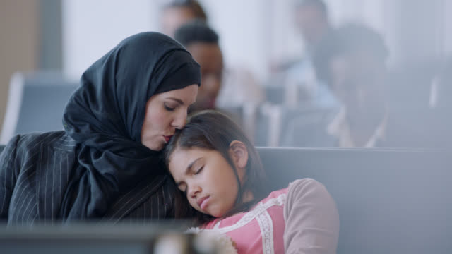 middle eastern mother kisses sleeping young daughter as they wait in airport terminal near gate. - gate stock videos & royalty-free footage