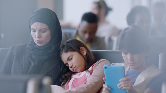 middle eastern mother, young daughter and son with smart phone rest in waiting area of airport terminal. - gate stock videos & royalty-free footage