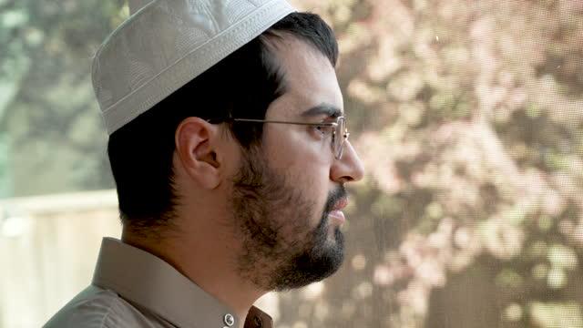 mellanöstern eftertänksam skäggig mellanöstern ung man tittar genom ett fönster - profil sedd från sidan bildbanksvideor och videomaterial från bakom kulisserna