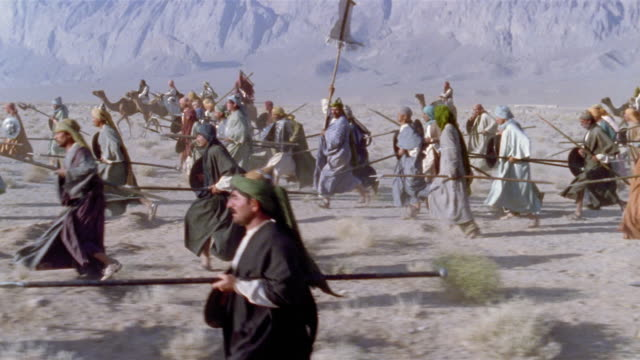 SLO MO WS REENACTMENT Middle Eastern warriors riding into battle on camels and running through desert brandishing swords and shields / Iran