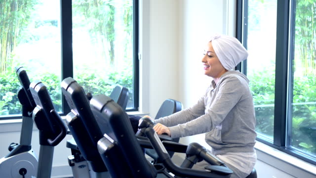 middle eastern woman exercising at the gym on bike - turban stock videos & royalty-free footage