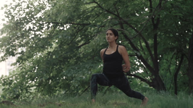 A middle eastern woman in her twenties practices Yoga, alone, outdoors