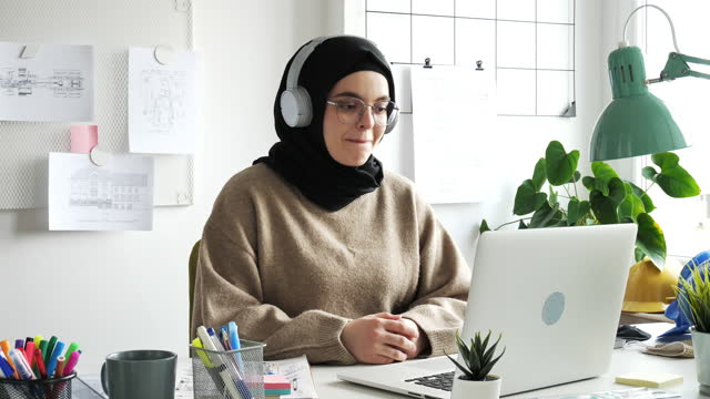 middle eastern woman with hijab and glasses having online business meeting in office - hijab stock videos & royalty-free footage