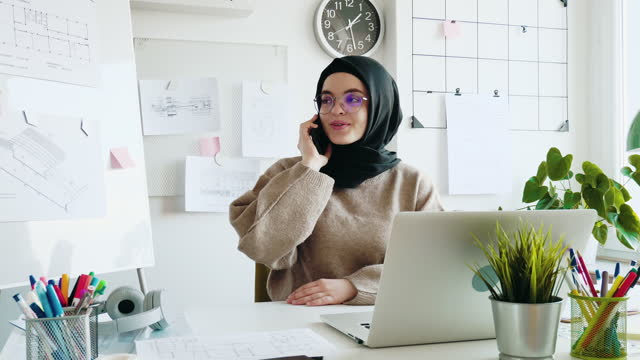 middle eastern woman working on laptop in office and answering the phone - hijab stock videos & royalty-free footage