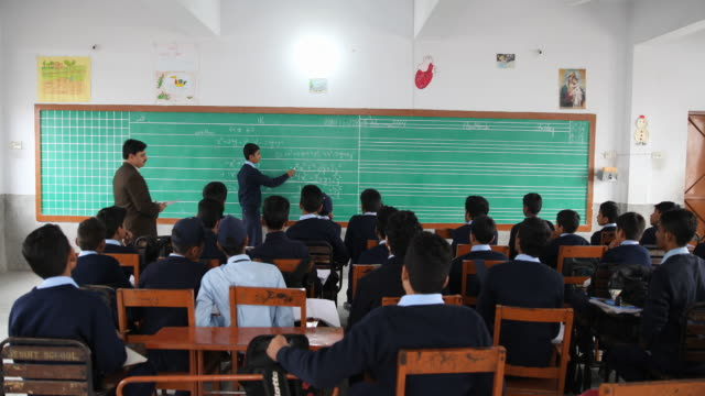 middle school boy wearing uniform explains polynomials on the blackboard to the rest of the class with supervision of the male teacher no - only boys stock videos and b-roll footage