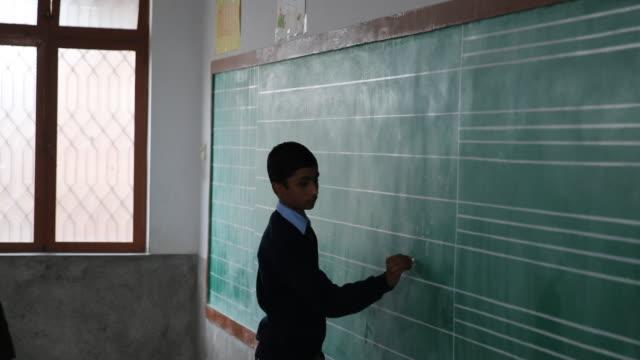 stockvideo's en b-roll-footage met middle school boy wearing uniform writes polynomials on the blackboard. no audio - alleen jongens