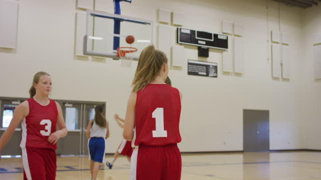 Middle school girls in basketball practice layup drill