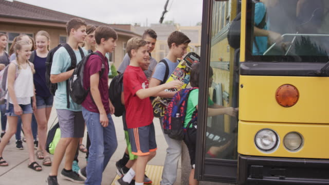 middle school students boarding a bus - bus stop stock videos & royalty-free footage