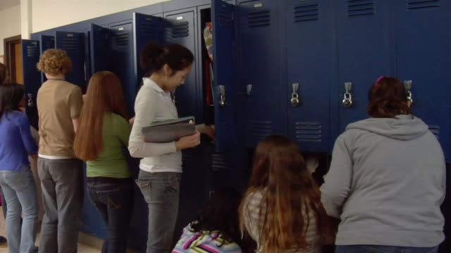stockvideo's en b-roll-footage met middle school students retrieve books and papers from their lockers. - lockerkast