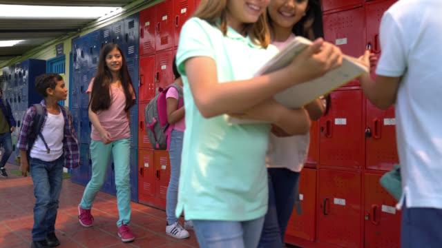 女子学生がノートをロッカーに置き片付けている間、ロッカーの前を歩く中学生 - ロッカー点の映像素材/bロール