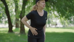 Middle shot of mid-adult woman suffering stomach cramps after jogging in summer park. Portrait of ill Caucasian sportswoman holding belly and leaving. Workout problems.