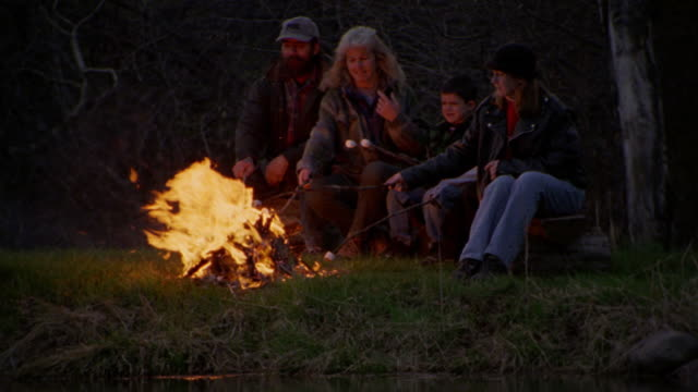 vídeos de stock, filmes e b-roll de middle-age couple + three children roasting marshmallows + blowing on them by pond at dusk / montana - fogueira de acampamento