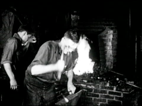 stockvideo's en b-roll-footage met blacksmith middleage male shaping forging hot horseshoe over anvil w/ hammer young adult male assistant bellowing fire bg cu male hands shaping hot... - smeden