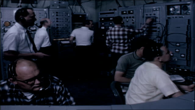 middle-aged adult caucasian men wearing headphones and working on equipment in control room. vs enormous receiver at goldstone / man seen climbing... - nasa video stock e b–roll