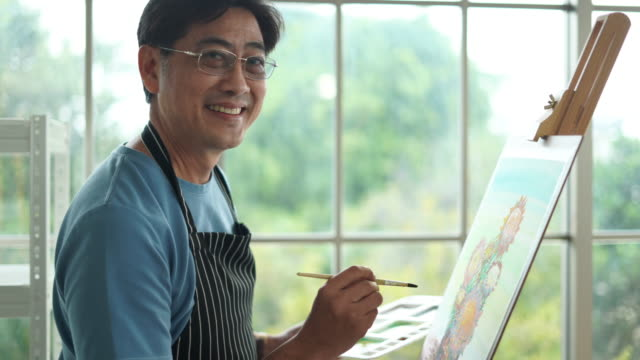 middle-aged asian man in a living room enjoying a hobby uses brush to painting nature with a happy smile - 画家点の映像素材/bロール