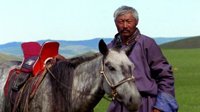 stockvideo's en b-roll-footage met ms portrait middle-aged asian man standing with horse nodding head / mongolia - mongolië