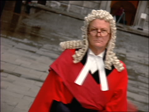 portrait middle-aged barrister in wig + robes turning to look at camera outdoors + smirking / london - lawyer stock videos & royalty-free footage