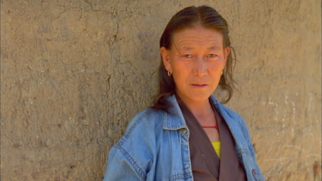 vídeos de stock e filmes b-roll de middle-aged bhutanese woman wearing denim jacket looks at camera available in hd. - jaqueta jeans