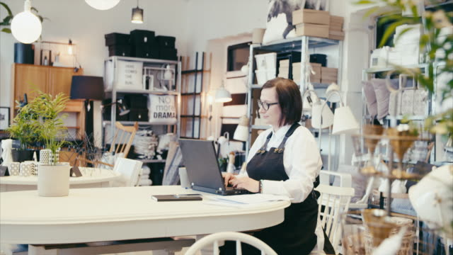 Middle-aged business owner doing finances in a home decor shop