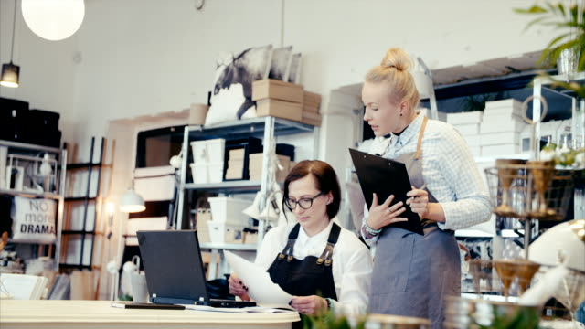 middle-aged business owner teaching young assistant how to do finances - scandinavian culture stock videos and b-roll footage