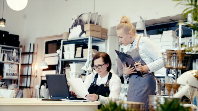 Middle-aged business owner teaching young assistant how to do finances (slow motion)