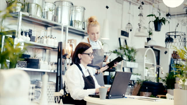 Middle-aged business owner teaching young assistant how to do finances
