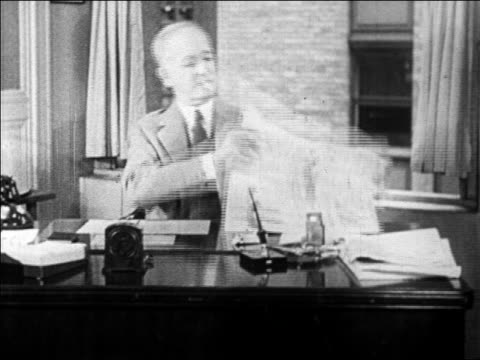 b/w 1929 middle-aged businessman at desk reading newspaper + smoking / newsreel - newspaper stock videos & royalty-free footage