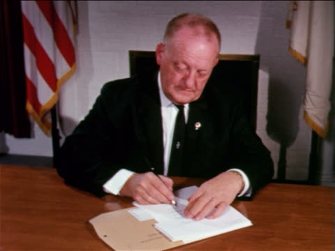 1962 middle-aged businessman signing documents at table / educational