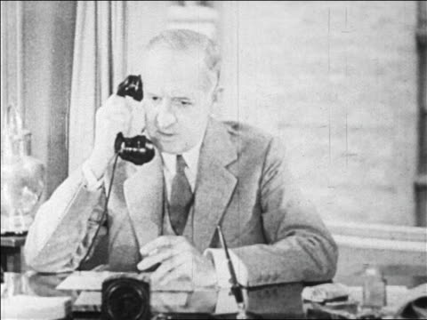 vídeos y material grabado en eventos de stock de b/w 1929 middleaged businessman smoking while talking on telephone in office / newsreel - vestimenta de negocios formal