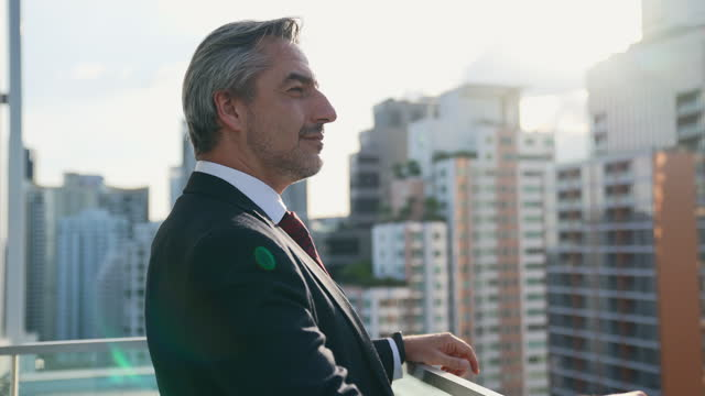 middle-aged businesspeople standing on the roof of the building he looked around with relaxation. represents leadership in a business suit. - 50 54 years stock videos & royalty-free footage