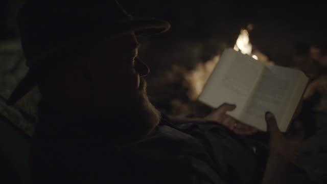 vidéos et rushes de d'âge mûr lectures mâles caucasiens de feu de camp - brightly lit