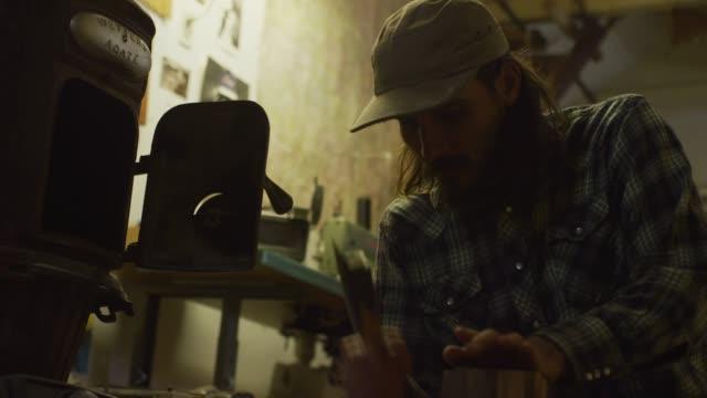 ワークショップの床にひざまずいている間、中年の白人男性が斧で丸太から kindling をチョップする - 刃物点の映像素材/bロール