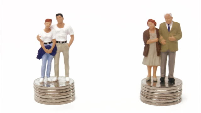Middle-aged couple and senior couple standing on pile of coins.