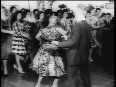 b/w 1961 middle-aged couple dancing the twist on dance floor as crowd looks on / newsreel - early rock & roll stock videos & royalty-free footage