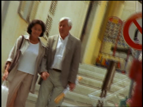 canted middle-aged couple holding hands carrying shopping bag + bread walk down stairs / corsica - mature couple stock videos & royalty-free footage
