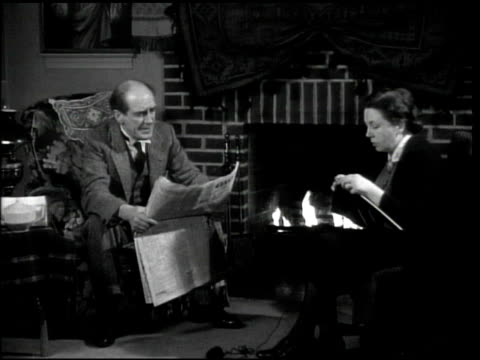 Middleaged couple sitting by fireplace man reading paper woman knitting 'Sacred Heart' painting of Christ BG male upset that Shaw agrees w/ his wife...