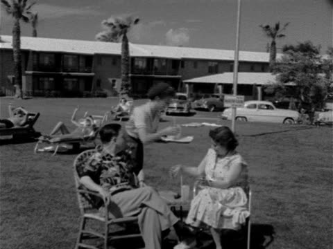 middleaged couple sitting in lawn chairs on grass outside hotel women in bathing suits reclining on beach chairs bg w/ cars parked in lot in front of... - waitress stock videos & royalty-free footage