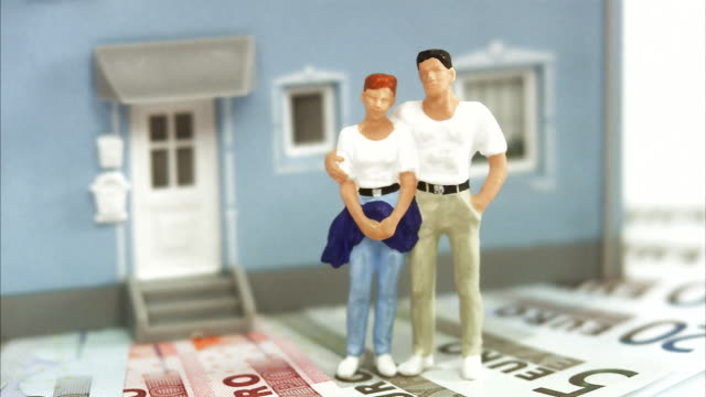 vídeos de stock, filmes e b-roll de middle-aged couple standing on bills in front of a house. - ornamento