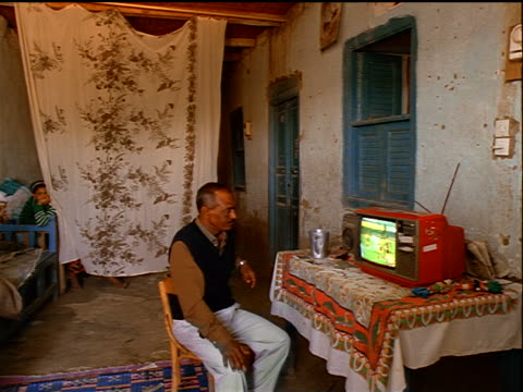 middle-aged egyptian man sitting watching small red tv on table in room / egypt - watching tv stock videos & royalty-free footage
