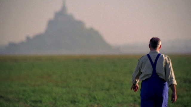 rear view middle-aged farmer walking towards mt. st. michel in background / normandy, france - bib overalls stock videos and b-roll footage