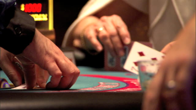middleaged female hand holding cards wiping cards on table signaling for another card card dealt body walking through frame signaling for another hit... - blackjack stock videos and b-roll footage